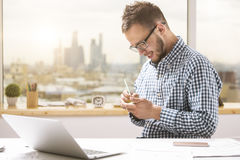 Sideview of young businessman taking notes. Side view of handsome young businessman in casual shirt and glasses taking notes at workplce Stock Images