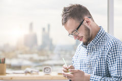 Sideview of young man taking notes. Side view of handsome young man in casual shirt and glasses taking notes at workplce Stock Photo
