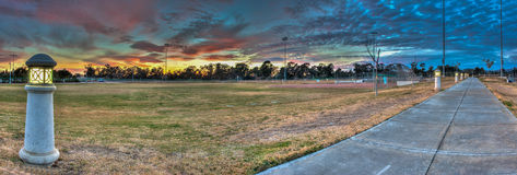 Sidewalk along softball field lit by lamps at dusk. Royalty Free Stock Image
