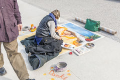 Sidewalk artist, man passing. Female pavement artist in Berlin, Germany. Man passing Royalty Free Stock Images