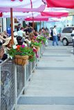 Sidewalk cafe. Behind a fence decorated with flowers full of people Stock Photo