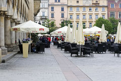 Sidewalk cafe on the old town square in Krakow. Krakow, Poland - May 25, 2017: Sidewalk cafe that is located on the old town square surrounded by historic Royalty Free Stock Photos