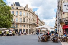 Sidewalk cafe and terrace in Bordeaux, France. Bordeaux, France - July 22, 2018: Sidewalk cafe and terrace in Cours de l`Intendance in historic centre of royalty free stock photo