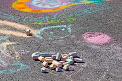 Sidewalk Chalk and Art. A pile of sidewalk chalk sits on the ground in front of bright colorful chalk art royalty free stock photo