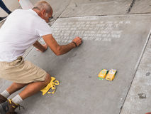 Sidewalk chalk artist writes poetry on stone plaza Stock Image