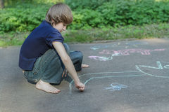 Sidewalk chalk drawings of barefoot teenage boy wearing blue t-shirt and jeans Royalty Free Stock Images