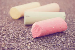 Sidewalk chalk. Four pieces of colorful sidewalk chalk on pavement, with selective focus on the pink chalk Royalty Free Stock Image