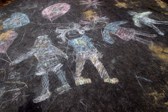 Sidewalk chalk of happy kids. Holding hands and carrying balloons Royalty Free Stock Image