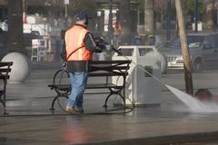 Sidewalk Cleanup. A city worker steam-cleans the sidewalk stock image