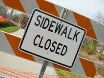 Sidewalk closed due to construction. Closed sign and barricade on gravel bike path because of construction. Barrier is white and orange stiped Stock Photo