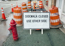 Sidewalk Closed Obstacle Course. What a mess! SIDEWALK CLOSED sign with several safety cones and orange and white barrier barrels and security netting Royalty Free Stock Photo