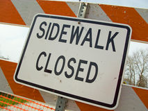 Sidewalk closed sign in construction zone. Closed sign and barricade on gravel bike path because of construction. Barrier is white and orange stiped royalty free stock photography
