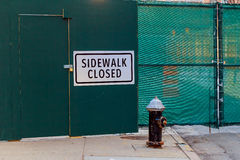 SIDEWALK CLOSED sign posted on green construction wall barrier Royalty Free Stock Photo