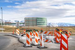 Sidewalk Closed sign and road safety poles on a paved road under repair. In the background is a modern building with skybridge and snowy mountain under a royalty free stock images
