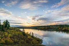 Sunrise in Edmonton with hot air balloon. Edmonton, Alberta autumn landscape with sunrise and hot air balloon and sky reflection in North Saskatchewan river royalty free stock images