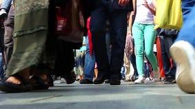 Sidewalk. The feet of dozens of pedestrians walking on the sidewalk stock video footage