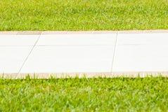 Sidewalk in the grass Stock Photos