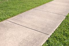 Sidewalk and grass. Detail of a concrete sidewalk with grass on both sides royalty free stock photos