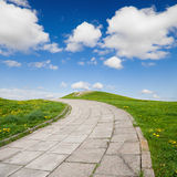 Sidewalk on green grass with blue sky Stock Photo