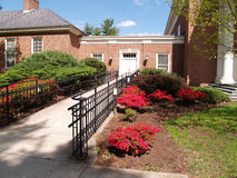 Sidewalk leading to a red brick building Stock Photos