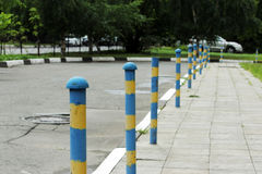 sidewalk near the house and blue yellow parking pole stationary strengthened against the entry of vehicles. Relevant when the dang Royalty Free Stock Images