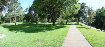 Sidewalk through park. Panoramic of the sidewalk running through a park stock image