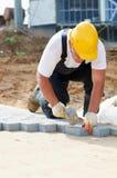 Sidewalk pavement construction works. Mason worker making sidewalk pavemant with stone blocks Stock Photo