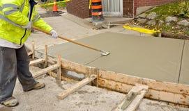 Sidewalk reconstruction. Worker smoothing wet cement on new sidewalk Stock Photos