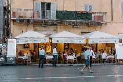 Sidewalk restaurant with tourists in Roman square a sunny summer. Rome, Italy - August 20, 2016: Sidewalk restaurant with tourists in Navona square in Rome a Royalty Free Stock Images