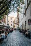 Sidewalk restaurant with tourists in Roman street a sunny summer Stock Images