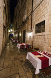 Sidewalk restaurants, Dubrovnik. DUBROVNIK, CROATIA - MAY 16, 2013: tables at night of a street restaurant in the old town of Dubrovnik. On 16 May 2013 in Stock Photography