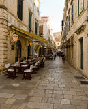 Sidewalk restaurants, Dubrovnik. DUBROVNIK, CROATIA - MAY 15, 2013: tables of a street restaurant in the old town of Dubrovnik. On 15 May 2013 in Dubrovnik Stock Photography