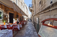 Sidewalk restaurants, Dubrovnik. DUBROVNIK, CROATIA - MAY 15, 2013: tables of a street restaurant in the old town of Dubrovnik. On 15 May 2013 in Dubrovnik Royalty Free Stock Photography