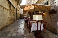 Sidewalk restaurants, Dubrovnik. DUBROVNIK, CROATIA - MAY 15, 2013: tables of a street restaurant in the old town of Dubrovnik. On 15 May 2013 in Dubrovnik Royalty Free Stock Photo