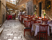 Sidewalk restaurants, Dubrovnik. DUBROVNIK, CROATIA - MAY 15, 2013: tables of a street restaurant in the old town of Dubrovnik. On 15 May 2013 in Dubrovnik Royalty Free Stock Photo