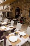 Sidewalk restaurants, Dubrovnik. DUBROVNIK, CROATIA - MAY 16, 2013: tables of a street restaurant in the old town of Dubrovnik. On 16 May 2013 in Dubrovnik Stock Photography