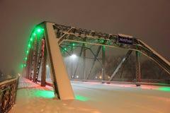 Sidewalk on Snow Coverd Bridge. Sidewalk at Night on a bridge over the Red River in a Blizzard. Sorlie Memorial Bridge in Grand Forks, North Dakota. Illuminated Royalty Free Stock Photo