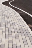 Sidewalk and street curve. Detail, stone patterns leading your way Royalty Free Stock Images