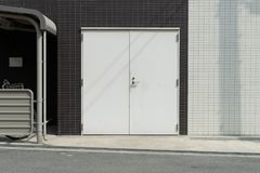 Roll up garage door on brick wall. Old weathered roll up garage door on brick wall royalty free stock photography