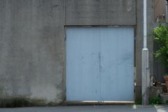 Roll up garage door on brick wall. Old weathered roll up garage door on brick wall royalty free stock images