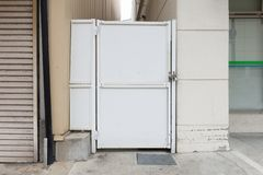 Roll up garage door on brick wall. Old weathered roll up garage door on brick wall stock image