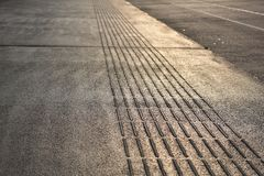 Sidewalk At Sunsrise Black White Yellow Morning Sun. Ordinairy sidewalk shot in the morning sun at a busstop in Amsterdam, The Netherlands. Made with a Nikon Stock Image