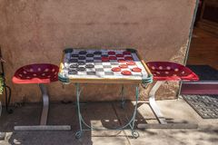 Sidewalk table with tractor seat chairs and checkerboard rug with giant checkers sitting beside stucco wall and open doorway royalty free stock photography