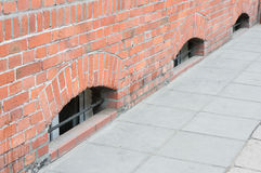 Sidewalk and a wall. Sidewalk made of tiles next to a wall with basement windows Royalty Free Stock Photo