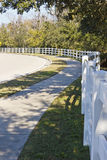 Sidewalk and white fence. Shady sidewalk and white fence along road Royalty Free Stock Photography