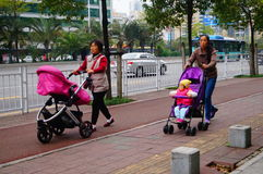 Sidewalk, women pushing baby carriages Stock Photos