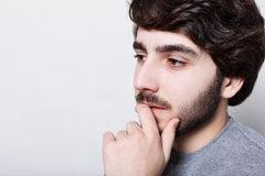 A sideways close-up of bearded thoughtful man with stylish haircut holding his hand on chin looking away at blank concrete wall. d. A sideways close-up of royalty free stock image