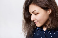 A sideways close-up of beautiful brunette with dark eyebrows, long eyelashes and pure skin dressed in dark shirt looking down with Stock Images