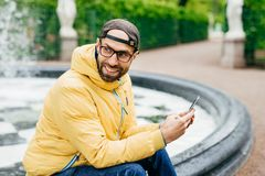 Sideways outdoor portrait of cheerful bearded stylish man in yellow jacket and eyeglasses sitting near fountain in park holding mo royalty free stock images