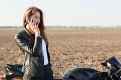 Sideways outdoor shot of attractive female biker has telephone conversation, stands near motorrbike, focused into distance, has wo royalty free stock photo